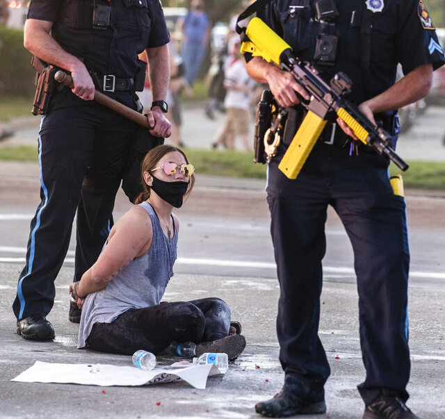 Omaha police arrest a woman for sitting in the eastbound lane of Dodge Street just west of 72nd Street, Friday, May 29, 2020, in Omaha, Neb. People were protesting the death of George Floyd who died in the custody of the Minneapolis police on Memorial Day. (Chris Machian/Omaha World-Herald via AP)