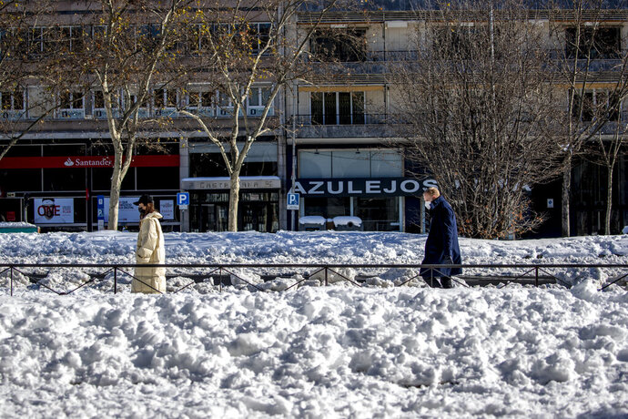 People walk along Paseo Castellana covered with the snow in Madrid, Spain, Monday, Jan. 11, 2021. The Spanish capital is trying to get back on its feet after a 50-year record snowfall that paralyzed large parts of central Spain over the weekend. (AP Photo/Manu Fernandez)