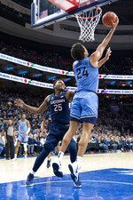 Villanova's Jeremiah Robinson-Earl, right, shoots the ball with Connecticut's Josh Carlton, left, defending during the first half of an NCAA college basketball game Saturday, Jan. 18, 2020, in Philadelphia. (AP Photo/Chris Szagola)