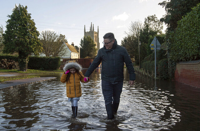 A man and girl walk through the flood water, in Great Barford, in Bedfordshire, England, Sunday, Dec. 27, 2020. Hurricane-force winds reaching up to 106 miles per hour (170 kph) and rainstorms battered parts of Britain, disrupting train services and stranding drivers in floodwaters. The Isle of Wight saw Storm Bella's strongest winds at 106mph, while parts of the south coast of England and north Wales also saw gusts of around 80mph (129 kph). (Joe Giddens/PA via AP)