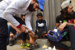 An injured person receives first aid during clashes between Iraqi security forces and anti-government demonstrators, in downtown Baghdad, Iraq, Wednesday, Nov. 13, 2019. (AP Photo/Hadi Mizban)