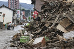 People walk near piled-up debris from a heavy rain in Hitoyoshi, Kumamoto prefecture, southern Japan Monday, July 6, 2020. Rescue operations continued and rain threatened wider areas of the main island of Kyushu. (Kyodo News via AP)