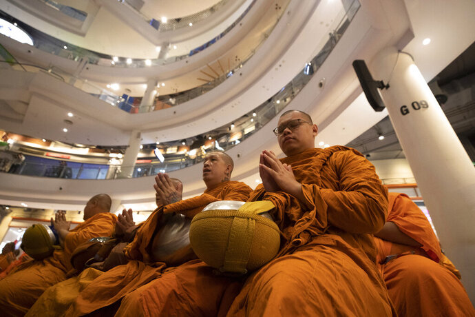 Buddhist monks pray during a ceremony to reopen the Terminal 21 shopping mall in Nakhon Ratchasima, Thailand, Thursday, Feb. 13, 2020. The worst-ever mass shooting in the country took place at the shopping mall over the weekend with a total of 29 people shot dead by a disgruntled soldier. (AP Photo/Sakchai Lalit)