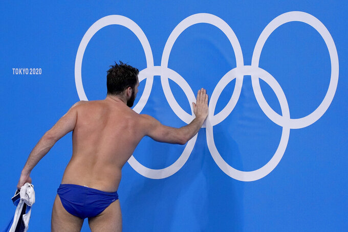 Greece's Konstantinos Genidounias touches the Olympic rings as he leaves the pool after a win over Hungary in a semifinal round men's water polo match at the 2020 Summer Olympics, Friday, Aug. 6, 2021, in Tokyo, Japan. (AP Photo/Mark Humphrey)