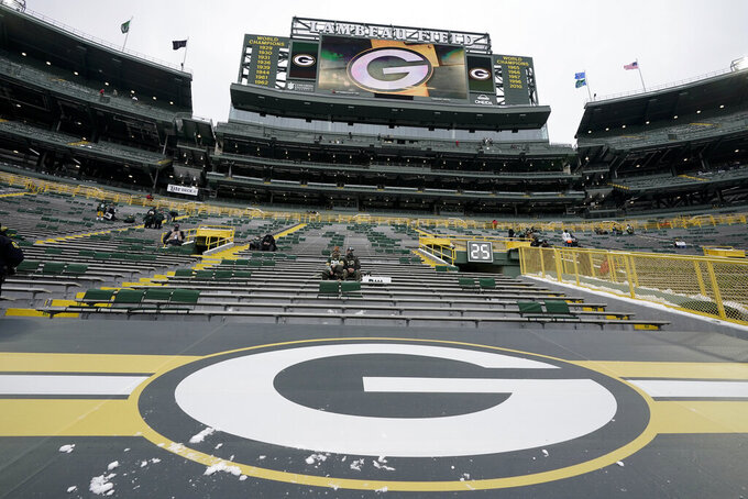 Fans, sitting socially distanced at Lambeau Field, wait for the NFC championship NFL football game between the Tampa Bay Buccaneers and Green Bay Packers in Green Bay, Wis., Sunday, Jan. 24, 2021. (AP Photo/Morry Gash)