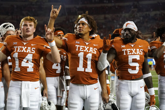 """Texas quarterback Casey Thompson (11) stands with his team as they sing """"The Eyes of Texas"""" after an NCAA college football game against Rice on Saturday, Sept. 18, 2021, in Austin, Texas. (AP Photo/Chuck Burton)"""