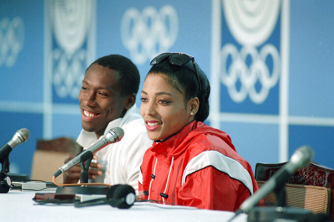 """FILE - Al Joyner, left, and Florence Griffith Joyner smile during a press conference at the Olympic Games in Seoul, in this Saturday, Sept. 17, 1988, file photo. For 33 years, sprinters have been chasing the records cemented next to the name """"Florence Griffith Joyner."""" The current wave of speedsters, few of them who were even born when the late Flo-Jo commanded the stage, keeps creeping closer to the late sprinter's hallowed marks in the 100 (10.49 seconds) and the 200 (21.34).  So much so that her husband, Al Joyner, firmly believes the records might soon fall — maybe over the next 10 days at the Tokyo Games.(AP Photo/Mark Duncan, File)"""