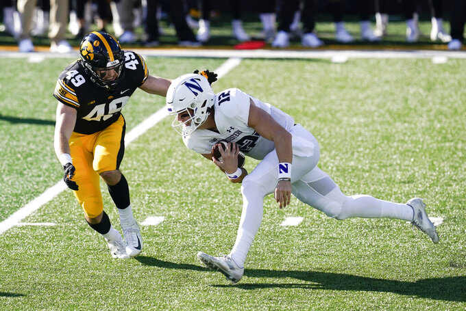 Northwestern quarterback Peyton Ramsey (12) runs from Iowa linebacker Nick Niemann (49) during the first half of an NCAA college football game, Saturday, Oct. 31, 2020, in Iowa City, Iowa. (AP Photo/Charlie Neibergall)