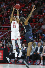 Utah guard Alfonso Plummer (25) shoots as Washington forward Hameir Wright (13) defends in the second half during an NCAA college basketball game Thursday, Jan. 23, 2020, in Salt Lake City. (AP Photo/Rick Bowmer)