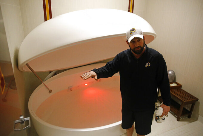 In this April 12, 2019, photo, Washington Redskins head athletic trainer Larry Hess demonstrates a salt water float orb inside a recovery room at the team's NFL football training facility in Ashburn, Va. With the use of state-of-the-art machines and techniques, the Redskins hope to cut down on injuries after leading the NFL in players on injured reserve last season. (AP Photo/Patrick Semansky)