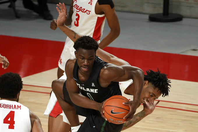 Tulane guard Sion James (1) grabs the ball away from Houston forward Brison Gresham, right, during the second half of an NCAA college basketball game, Saturday, Jan. 9, 2021, in Houston. (AP Photo/Eric Christian Smith)