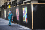 A pedestrian passes newly installed posters on a shuttered businesses in Philadelphia, Monday, May 4, 2020. The Center City District and Mural Arts Philadelphia posted the original works on multiple locations in an effort to enhance the neighborhood awash with business shuttered to help curb the spread of coronavirus. (AP Photo/Matt Rourke)
