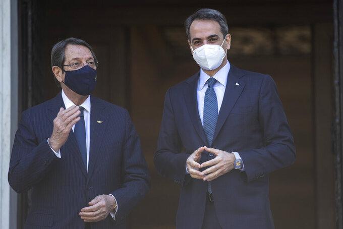 Greece's Prime Minister Kyriakos Mitsotakis, right, welcomes Cypriot President Nicos Anastasiades before their meeting at Maximos Mansion in Athens,Wednesday, April 21, 2021. (AP Photo/Petros Giannakouris)