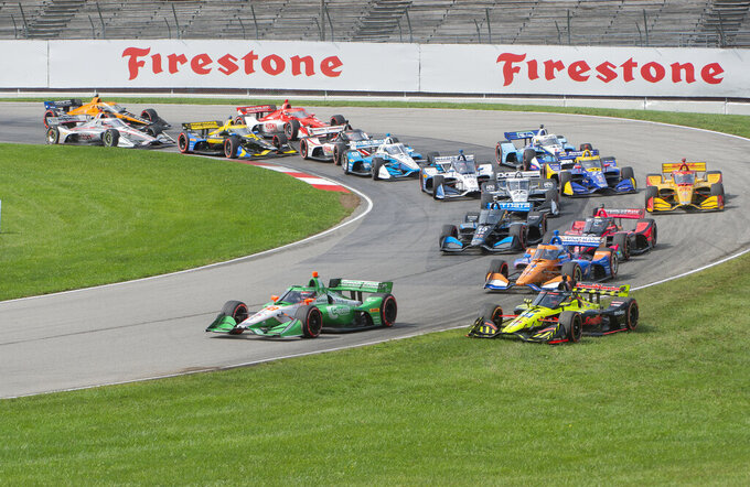Colton Herta (88) leads the field as Santino Ferrucci (18) runs in the grass during the start of an IndyCar Series auto race at Mid-Ohio Sports Car Course, Sunday, Sept. 13, 2020, in Lexington, Ohio. (AP Photo/Phil Long)