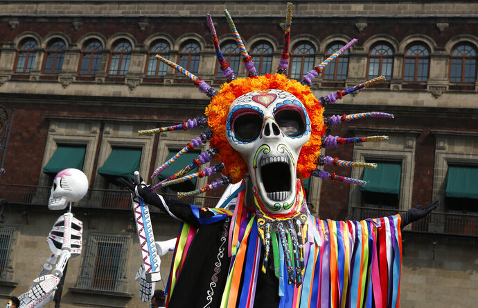 """Performers in costume attend a Day of the Dead parade in Mexico City, Sunday, Oct. 27, 2019. The parade on Sunday marks the fourth consecutive year that the city has borrowed props from the opening scene of the James Bond film, """"Spectre,"""" in which Daniel Craig's title character dons a skull mask as he makes his way through a crowd of revelers. (AP Photo/Ginnette Riquelme)"""