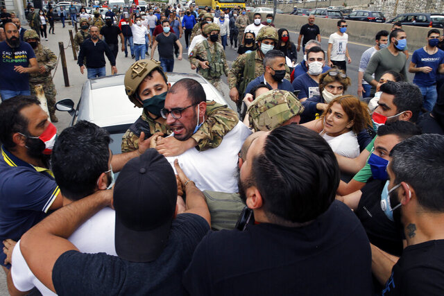 Anti-government protesters scuffle with Lebanese army soldiers in the town of Zouk Mosbeh, north of Beirut, Lebanon, Monday, April 27, 2020. Scattered anti-government protests broke out in several parts of Lebanon on Monday amid a crash in the local currency and a surge in food prices, leading to road closures that prevented medical teams from setting out from Beirut to conduct coronavirus tests across the country. (AP Photo/Bilal Hussein)