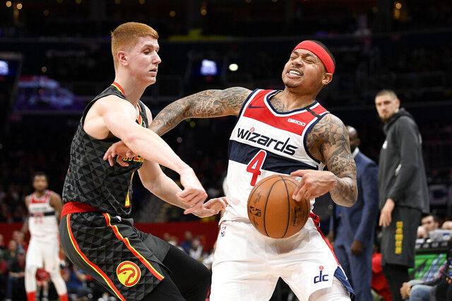 Atlanta Hawks guard Kevin Huerter (3) reaches for the ball next to Washington Wizards guard Isaiah Thomas (4) during the first half of an NBA basketball game, Friday, Jan. 10, 2020, in Washington. (AP Photo/Nick Wass)