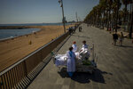 Francisco Espana, 60, is surrounded by members of his medical team as he looks at the Mediterranean sea from a promenade next to the