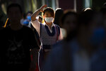 A woman wearing a face mask to protect against the coronavirus is caught in the sunlight as she walks along a street in Beijing, Friday, Sept. 18, 2020. Even as China has largely controlled the outbreak, the coronavirus is still surging across other parts of the world. (AP Photo/Mark Schiefelbein)