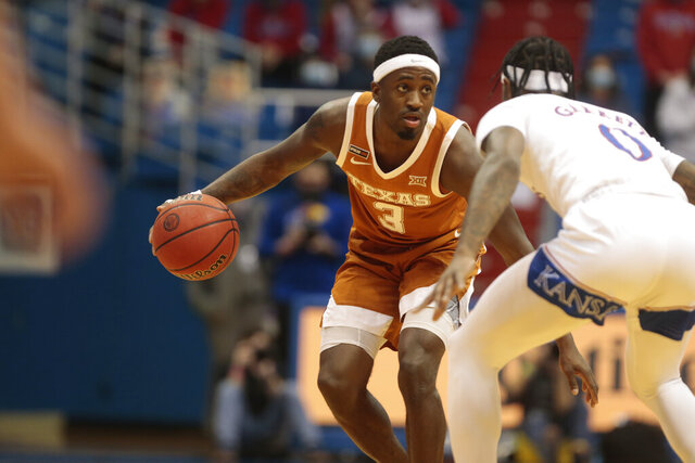 Texas junior guard Courtney Ramey looks to make a pass against Kansas in the first half of an NCAA college basketball game  Saturday, Jan. 2, 2021, in Lawrence, Kan. (Evert Nelson//The Topeka Capital-Journal via AP)