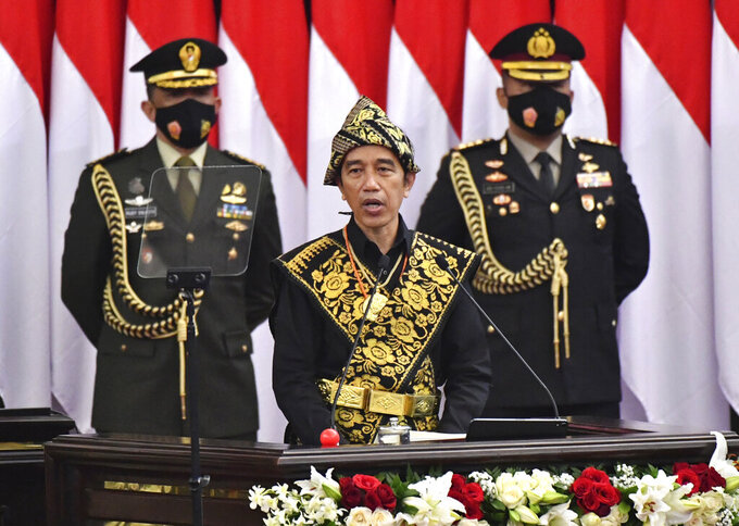 In this photo released by Indonesian Presidential Palace, Indonesian President Joko Widodo, center, dressed in a traditional outfit, delivers his national address before the parliament members in Jakarta, Indonesia, Friday, Aug. 14, 2020. Indonesia's president called on all citizens to turn the COVID-19 crisis into an advancement opportunity and pledged health care reforms in an address Friday ahead of the country's 75th anniversary of independence. (Agus Suparto/Presidential Palace via AP)