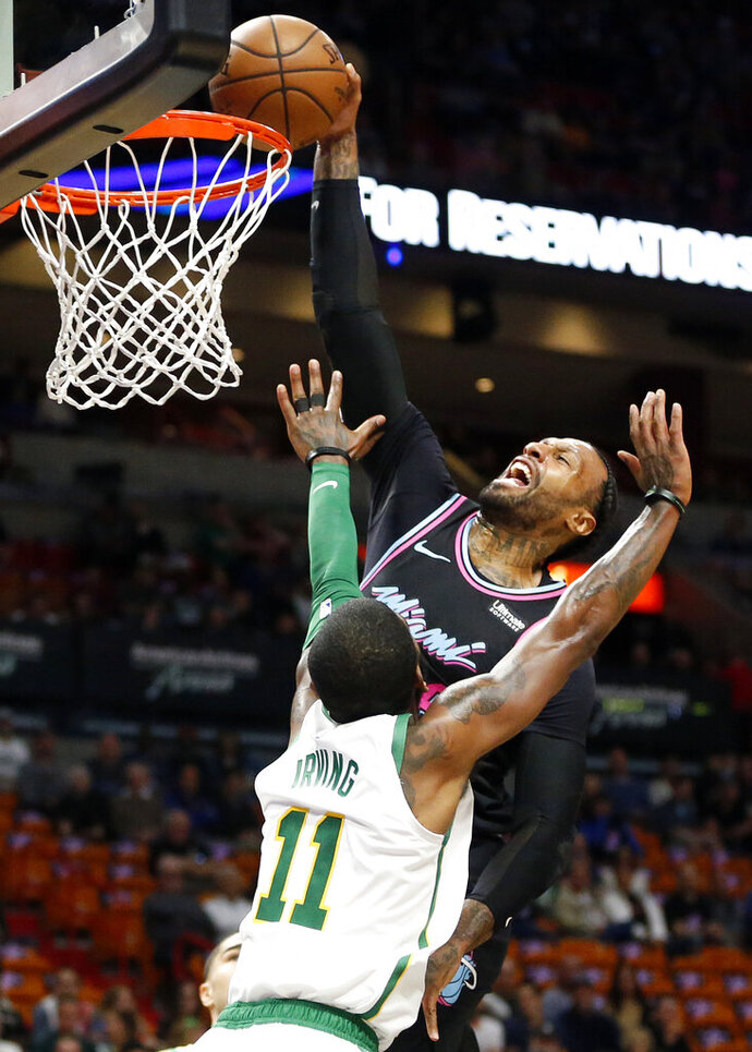 Miami Heat forward James Johnson, top, goes to the basket against Boston Celtics guard Kyrie Irving (11) during the first half of an NBA basketball game, Thursday, Jan. 10, 2019, in Miami. (AP Photo/Joel Auerbach)