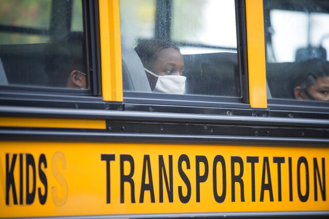 Students arrive by bus at Foundation Preparatory School for their return to school during the coronavirus in New Orleans on Monday, Oct. 12, 2020. It was the first day of in-person learning for fifth-12th grade public school students in Orleans Parish. (Chris Granger/The Times-Picayune/The New Orleans Advocate via AP)