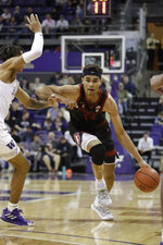 Stanford's Oscar da Silva, right, tries to get past Washington's RaeQuan Battle during the first half of an NCAA college basketball game Thursday, Feb. 20, 2020, in Seattle. (AP Photo/Elaine Thompson)