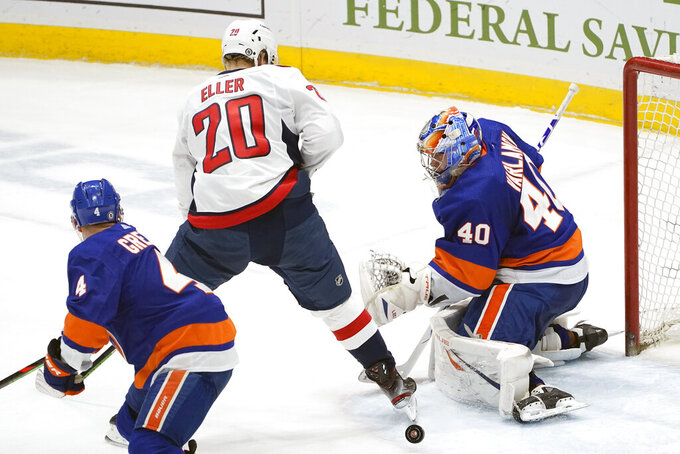 New York Islanders goaltender Semyon Varlamov (40) makes a save with Washington Capitals center Lars Eller (20) in front of the crease and Islanders defenseman Andy Greene (4) watching during the second period of an NHL hockey game Thursday, April 22, 2021, in Uniondale, N.Y. (AP Photo/Kathy Willens)