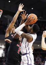 Northwestern forward Vic Law, right, shoots as Rutgers center Shaquille Doorson, center, and guard/forward Ron Harper Jr., try to block the ball during the second half of an NCAA college basketball game, Wednesday, Feb. 13, 2019, in Evanston, Ill. Rutgers won 59-56. (AP Photo/Nam Y. Huh)