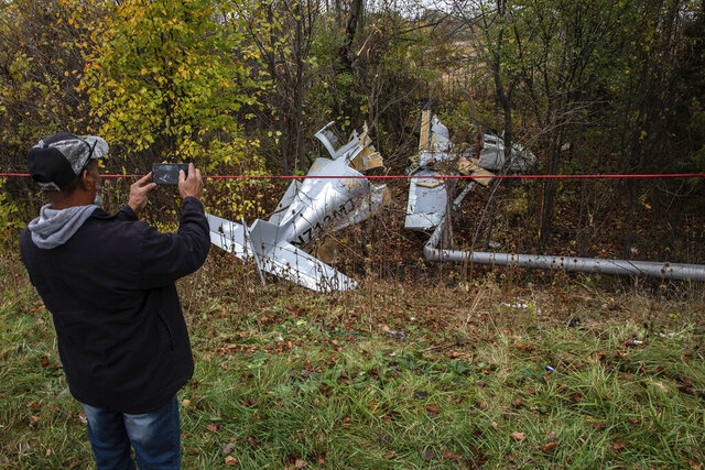 A person takes a picture of the site where a small plane crashed the night before into a wooded area off of Lincoln Highway, just west of Interstate 394 in Ford Heights, Ill., on Wednesday, Oct. 21, 2020. Authorities say a suburban Chicago man who was seriously injured when the plane he was piloting crashed along the highway Tuesday later died from his injuries. (Zbigniew Bzdak/Chicago Tribune via AP)