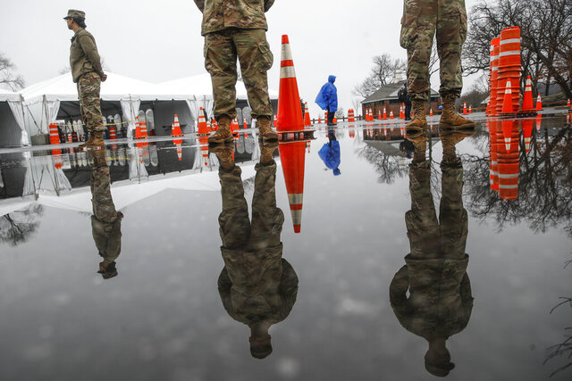 "National Guard personnel stand at attention as they wait for patients to arrive for COVID-19 coronavirus testing facility at Glen Island Park, Friday, March 13, 2020, in New Rochelle, N.Y.  State officials have set up a ""containment area"" in the New York City suburb, where schools and houses of worship are closed within a 1-mile radius of a point near a synagogue where an infected person with coronavirus had attended events. State officials stress it is not a lockdown. The vast majority of people recover from the new coronavirus. According to the World  Health Organization, most people recover in about two to six weeks, depending on the severity of the illness. (AP Photo/John Minchillo)"