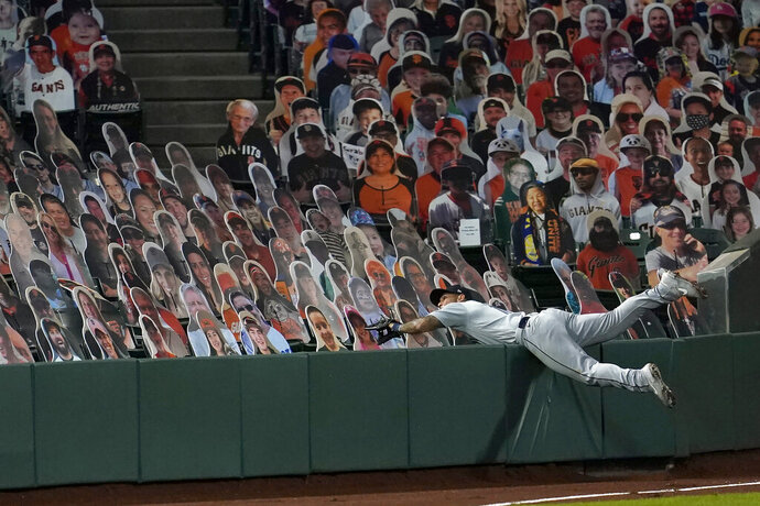 Seattle Mariners left fielder Tim Lopes reaches into seats occupied by cutouts while unsuccessfully trying to catch a foul by hit by San Francisco Giants' Wilmer Flores during the third inning of a baseball game in San Francisco, Wednesday, Sept. 16, 2020. This is a makeup of a postponed game from Tuesday in Seattle. (AP Photo/Jeff Chiu)