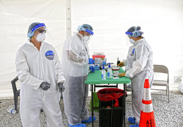 Banyan Medical Systems health workers wait to test citizens at the coronavirus antibody test drive through site in Bal Harbour Shops as the Novel coronavirus pandemic continues on Wednesday, May 13, 2020 in Bal Harbour.(David Santiago/Miami Herald via AP)