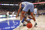 Pittsburgh's Eric Hamilton, bottom, dives for a loose ball under North Carolina's Armando Bacot during the first half of an NCAA college basketball game, Saturday, Jan. 18, 2020, in Pittsburgh. (AP Photo/Keith Srakocic)