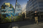 People walk past next to a pro-Europe street art painting in the European quarter in Brussels, Friday, Oct. 25, 2019. EU ambassadors agreed on Friday on the principle of granting Britain's request for another extension to the Brexit deadline but have yet to find a consensus on the length of the new delay. (AP Photo/Francisco Seco)