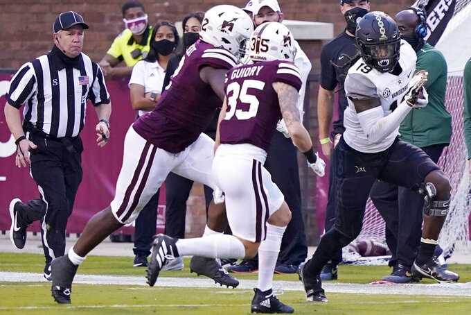 Vanderbilt wide receiver Chris Pierce Jr. (19) tries to elude a tackle by Mississippi State defenders, including safety Landon Guidry (35), during the second half of an NCAA college football game in Starkville, Miss., Saturday, Nov. 7, 2020. (AP Photo/Rogelio V. Solis)