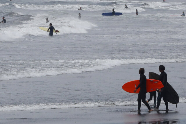 A couple of surfers walks on Katase Kaigan beach in Fujisawa, near Tokyo, Tuesday, April 21, 2020.  Japan's Prime Minister Shinzo Abe expanded a state of emergency to all of Japan from just Tokyo and other urban areas as the virus continues to spread. (AP Photo/Koji Sasahara)