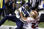 Seattle Seahawks' DK Metcalf, left, is wrapped up by San Francisco 49ers' Ahkello Witherspoon as he comes down with a touchdown reception in the end zone during the second half of an NFL football game, Sunday, Dec. 29, 2019, in Seattle. (AP Photo/Ted S. Warren)