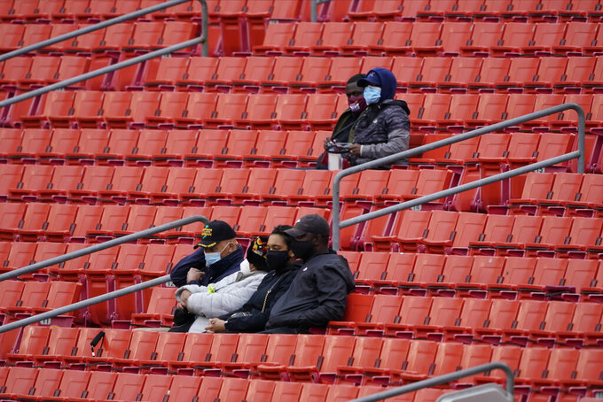Fans sits and watch the first half of an NFL football game between the Dallas Cowboys and Washington Football Team, Sunday, Oct. 25, 2020, in Landover, Md. (AP Photo/Susan Walsh)