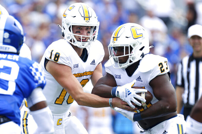 Chattanooga quarterback Cole Copeland (18) hands the ball off to running back Tyrell Price (23) during the first half of a NCAA college football game against Kentucky in Lexington, Ky., Saturday, Sept. 18, 2021. (AP Photo/Michael Clubb)