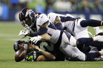 Seattle Seahawks quarterback Paxton Lynch, lower left, loses the ball as he falls under Denver Broncos cornerback DeVante Bausby (41) during the second half of an NFL football preseason game, Thursday, Aug. 8, 2019, in Seattle. (AP Photo/Stephen Brashear)
