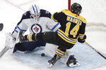 Winnipeg Jets goaltender Laurent Brossoit (30) makes a save on a shot by Boston Bruins right wing Chris Wagner (14) during the first period of an NHL hockey game Thursday, Jan. 9, 2020, in Boston. (AP Photo/Elise Amendola)