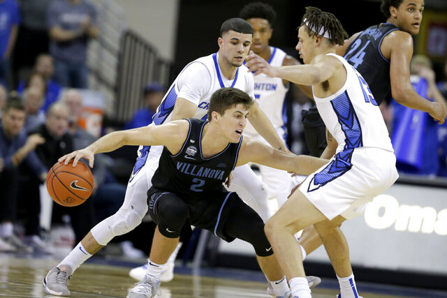 Villanova's Collin Gillespie (2) is defended by Creighton's Christian Bishop (13) and Marcus Zegarowski (11) during the second half of an NCAA college basketball game in Omaha, Neb., Tuesday, Jan. 7, 2020. Villanova won 64-59. (AP Photo/Nati Harnik)