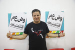 FILE - In this Aug. 29, 2019 file photo, Ayman Odeh, the leader of the Arab Joint List parties, poses for a photo in party offices in Nazareth, Israel. An unprecedented repeat election next week provides no guarantee that the do-over vote will produce a more decisive result than an inconclusive one last April. Arabic on posters reads :