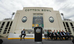 NHL commissioner Gary Bettman speaks from the podium with others looking on during a news conference outside the Cotton Bowl in Dallas, Wednesday, March 20, 2019. Bettman and the group were on hand to announce the NHL Winter Classic hockey game between the Nashville Predators and the Dallas Stars to be played Jan. 1, 2020, at the Cotton Bowl in Dallas. (AP Photo/LM Otero)