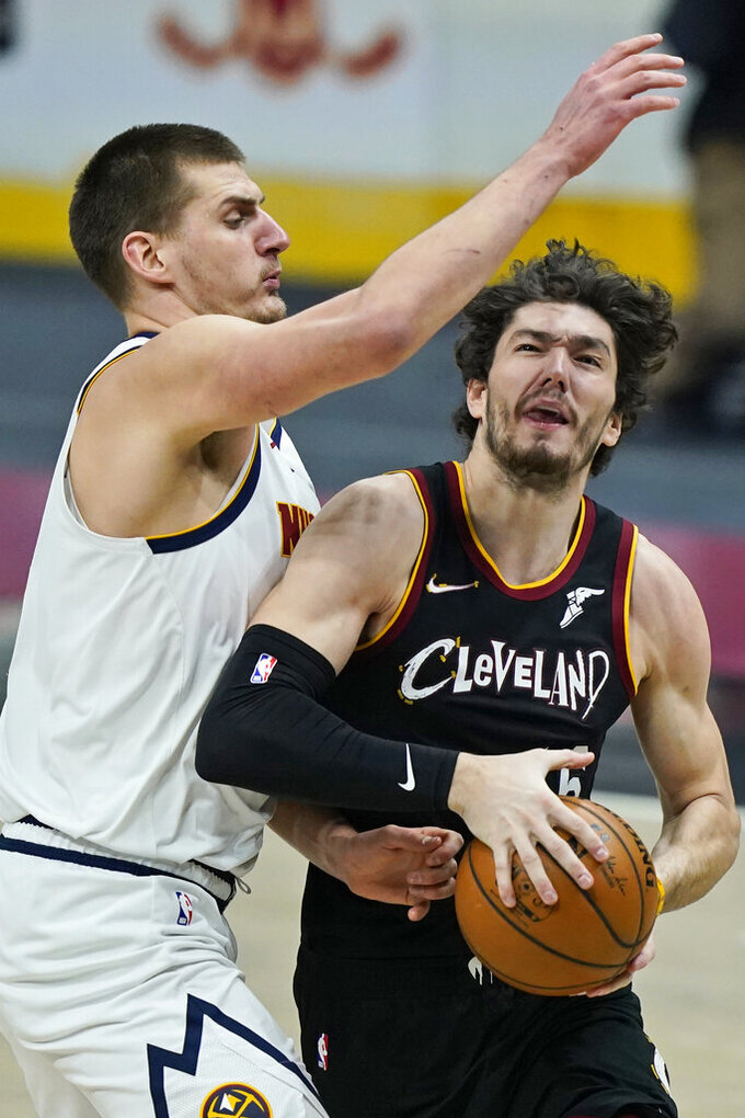 Cleveland Cavaliers' Cedi Osman, right, drives as Denver Nuggets' Nikola Jokic defends during the first half of an NBA basketball game Friday, Feb. 19, 2021, in Cleveland. (AP Photo/Tony Dejak)
