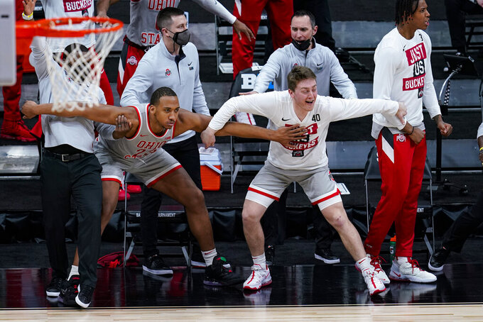 The Ohio State bench, including forward Zed Key (23) and guard Jansen Davidson Jr. (40) celebrate in the first half of an NCAA college basketball game against Minnesota at the Big Ten Conference tournament in Indianapolis, Thursday, March 11, 2021. (AP Photo/Michael Conroy)