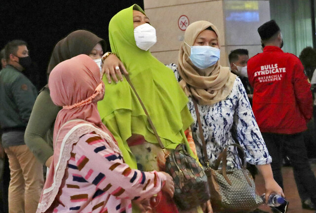Relatives of passengers arrive at a crisis center set up following a report that a Sriwijaya Air passenger jet has lost contact with air traffic controllers shortly after take off, at Soekarno-Hatta International Airport in Tangerang, Indonesia,Saturday, Jan. 9, 2021. The Boeing 737-500 took off from Jakarta with 56 passengers and six crew members onboard, and lost contact with the control tower a few moments later. (AP Photo/Tatan Syuflana)