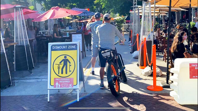 Pedestrians and cyclists walk through a pathway between outdoor dining areas that have largely taken over State Street in downtown Santa Barbara, Calif., Wednesday, July 29, 2020. After weeks of stressing education over enforcement, California communities say they are now issuing fines and relying on anonymous tips to make sure businesses and residents are complying with health orders requiring masks, disinfection, and social distancing as the state tries to contain the coronavirus. (John Palminteri/KEYT-TV via AP